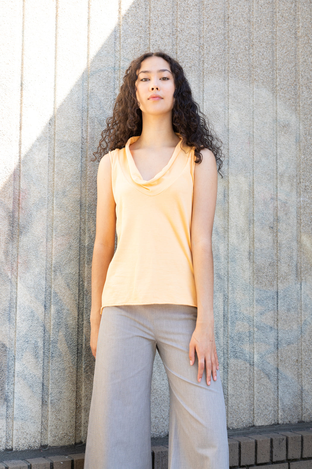 Photo of a lightweight, scoop, cowl neck t-shirt composed of 100% organic cotton jersey in a soft orange color.