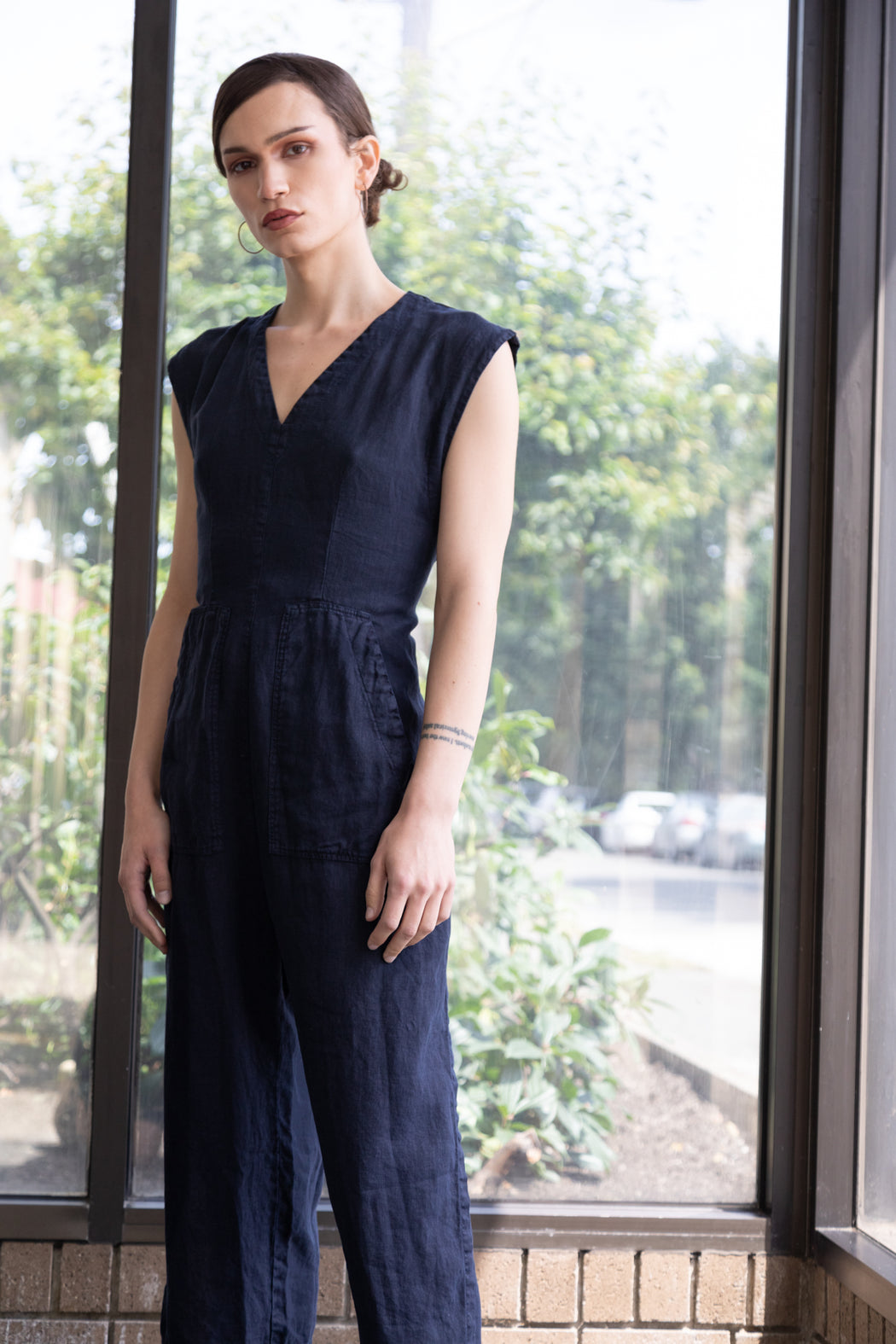 Photo of a dark blue linen jumpsuit with ties for adjustable wearing and sizing.