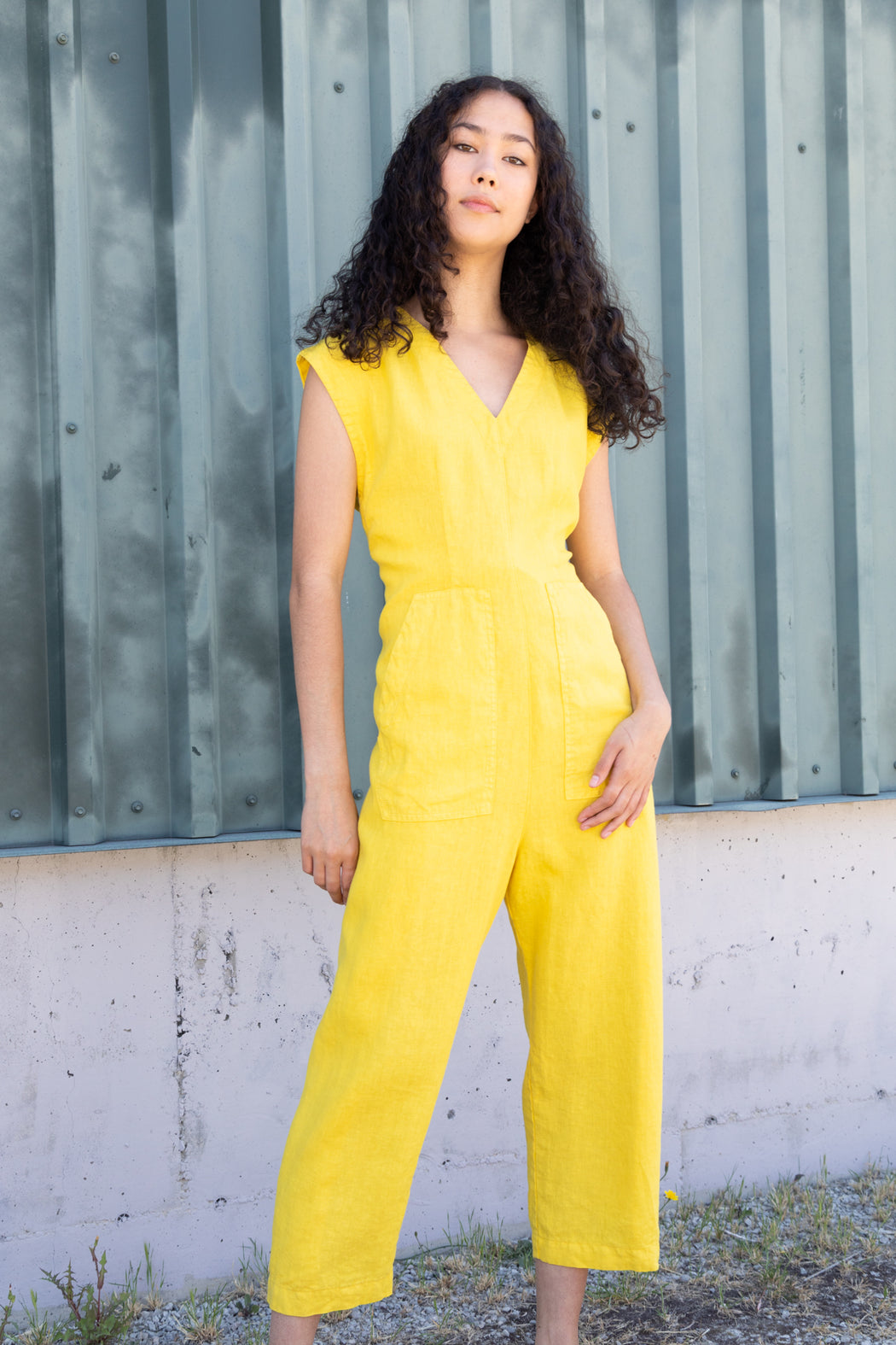 Photo of a bright yellow linen jumpsuit with ties for adjustable wearing and sizing.