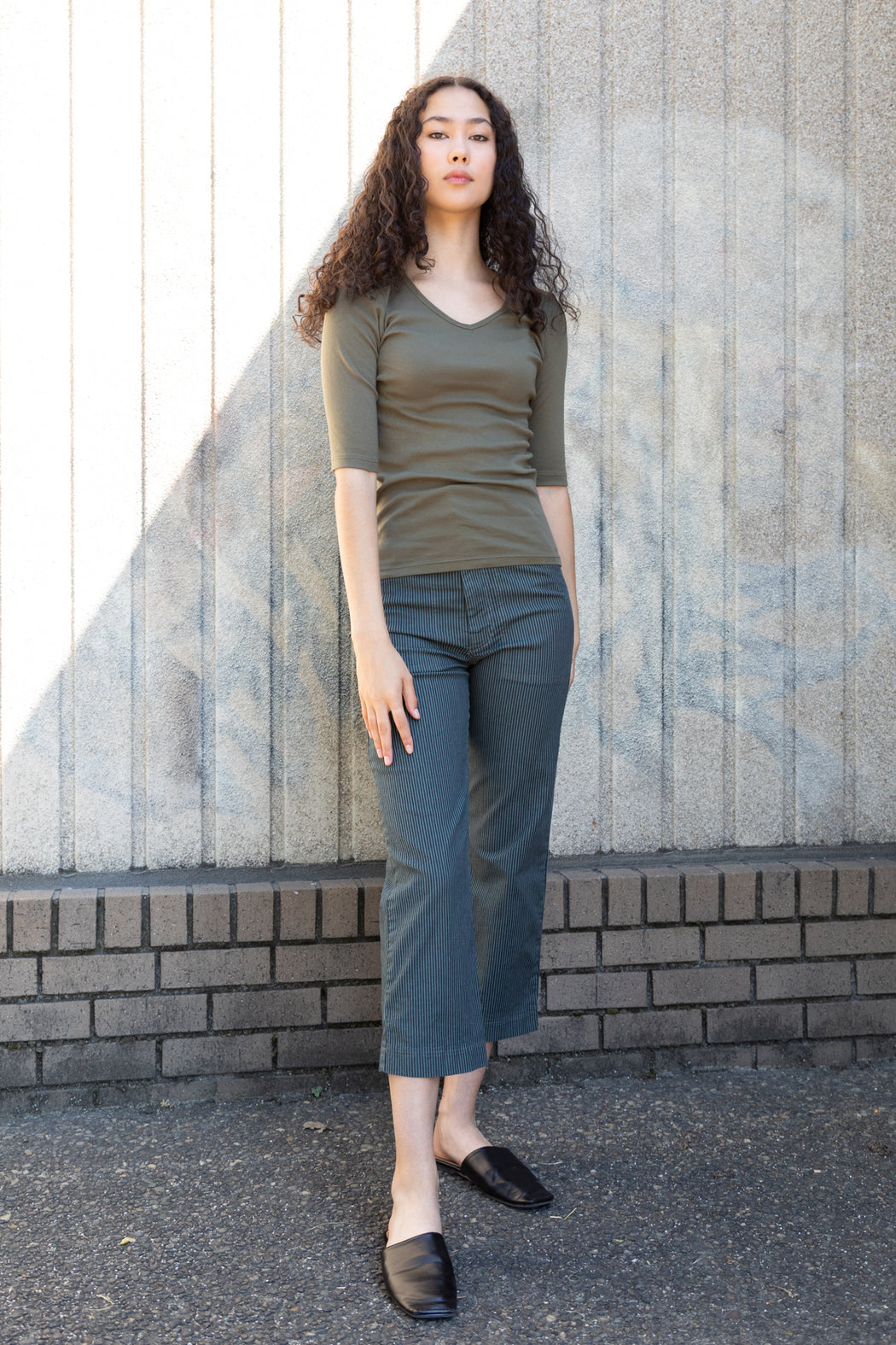 Photo of a 100% organic cotton tee in army green with a v-neck and elbow length sleeves.