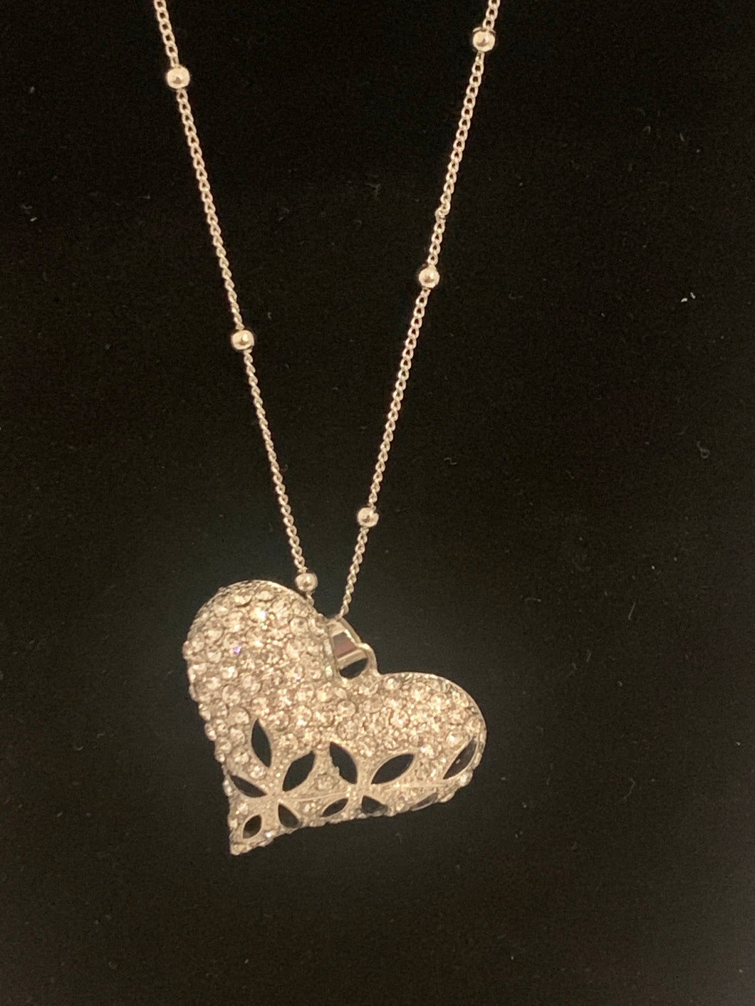 Silver heart necklace with detailed chain.