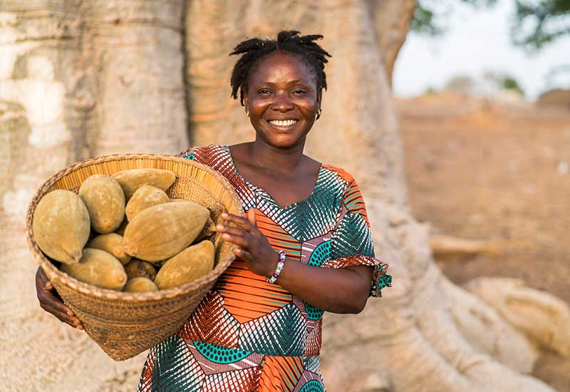 Aduna Baobab Producer, Lardi, with basket of fruits