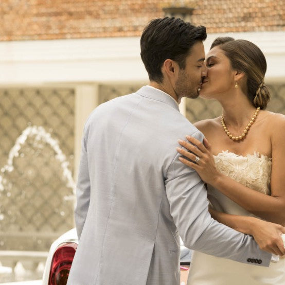 Groom and bride kissing. Bride is wearing Jewelmer Swan dangling earrings and Jewelmer strand necklace.