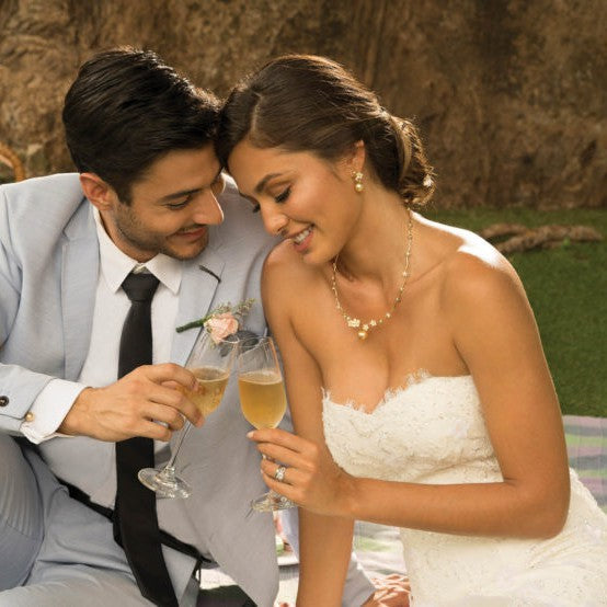 Groom and bride toasting champagne. Bride is wearing Jewelmer Spring Blossoms dangling earrings and Jewelmer Spring Blossoms necklace.