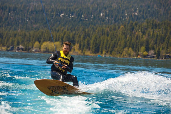 Wake surfing in Lake Tahoe on a wooden surf board
