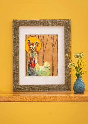 Matted image of a llama with halo, matted in  white with a driftwood frame sitting on a shelf with yellow background.
