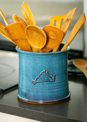 Blue hand thrown pottery utensil bucket with Martha's Vineyard shape on the side filled with wooden spoons sitting on a kitchen counter.