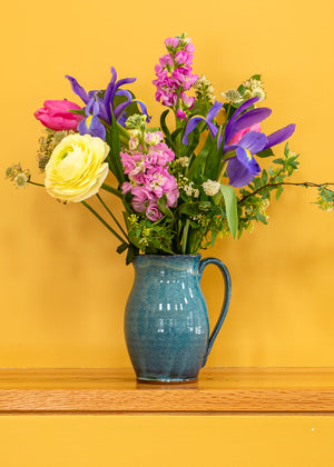 Blue stoneware pitcher in blue glaze with graceful handle holding assorted fresh flowers sitting on a shelf with yellow background.
