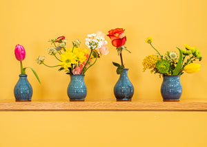 Four blue stoneware bud vases  with fresh flowers in a row on a shelf with a yellow background.