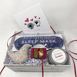 Gift box with an herbal sleep mask, scented dove, soy candle, and other gift items.