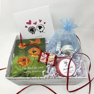 Open gift box with white shred, candle, inspirational books, lip care kit, and soap.