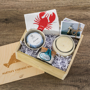 Small wooden box containing a candle, photo cards, soap, sea salt, and a tea towel.