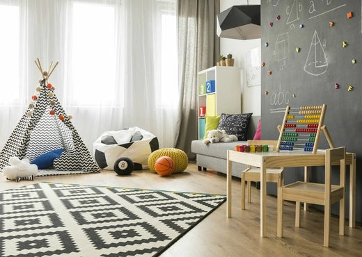 kids room decor, patterned rug, wood table, teepee & toys in front of white curtains