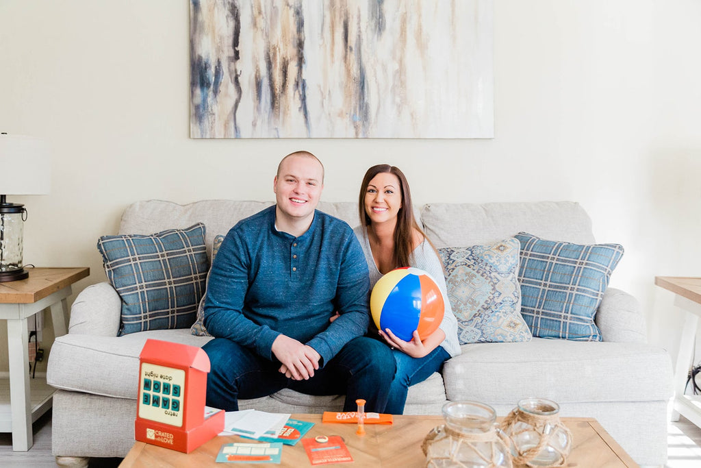 Crated with Love founders, Tyler and Michelle, sitting on a couch with one of our date night boxes