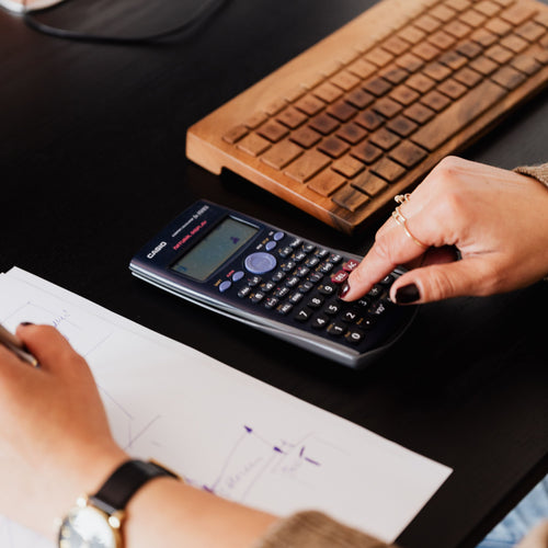 Collection and organization of finances based on general business and tax categories.  -Available as a monthly, quarterly and annual service-). Woman writing on paper and using calculator.