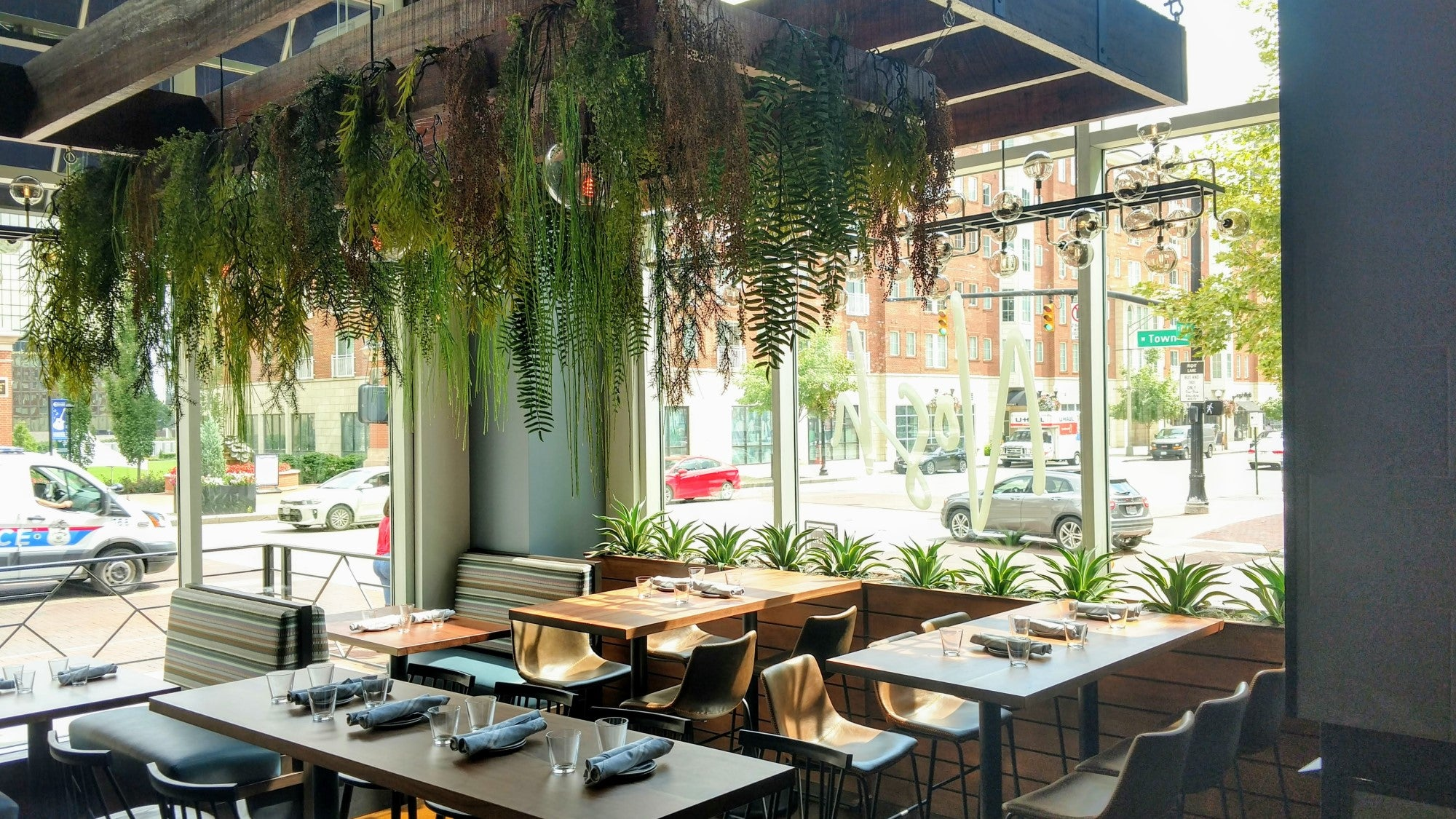 Hanging garden in restaurant composed of faux plants. Live agave plants in window boxes.