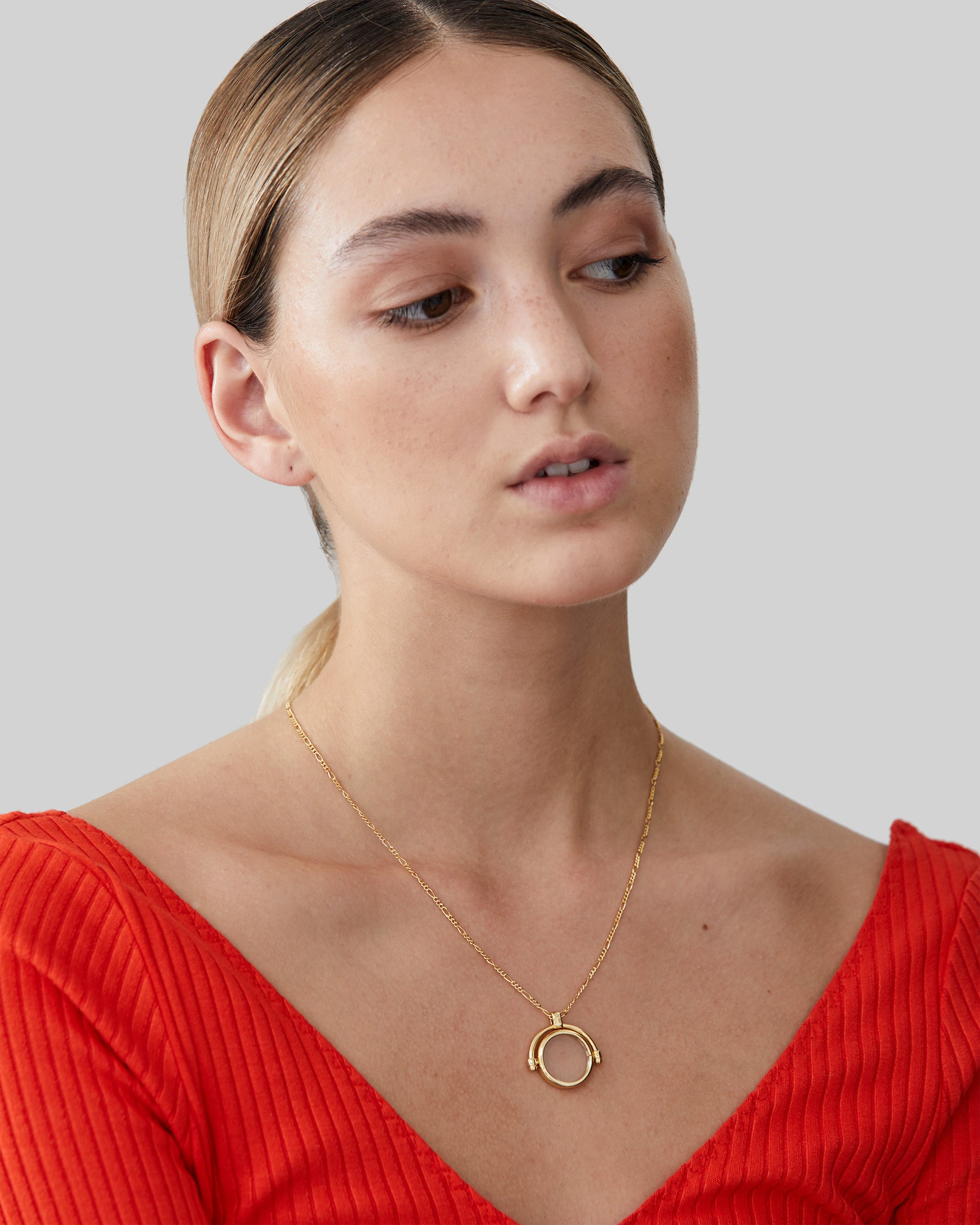 North North North 12 carat thin gold figaro necklace with a transparent disc set in a gold frame, Colonel
