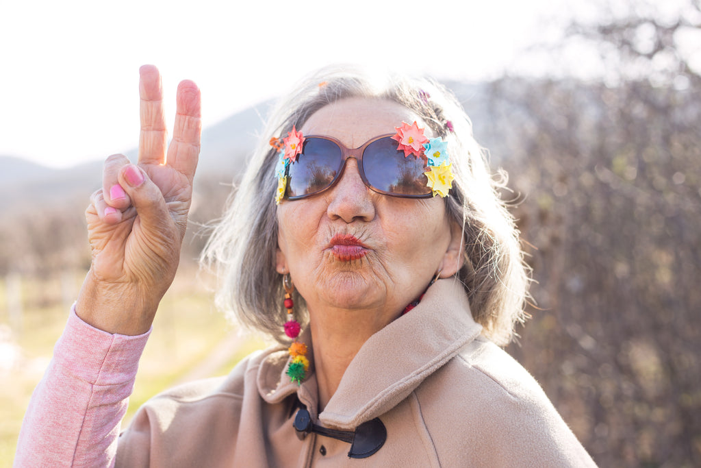Older woman with fun, flower sunglasses outside blowing a kiss and showing peace sign with fingers.