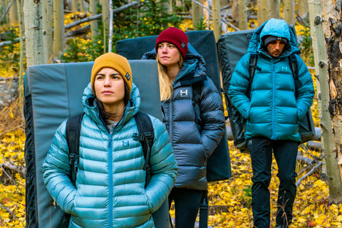Three people walking in Altocumulous Down Jackets and Backcountry Beanies by HIMALI with crashpads on their back for an epic bouldering adventure.