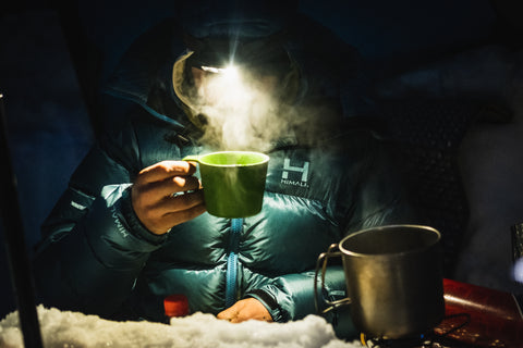 Man drinking a Steaming Mug of tea in an Altitude Parka by HIMALI shot by Rhett H.B. Gause