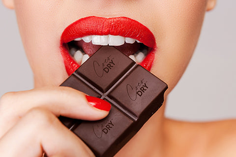 Woman with red lipstick and white teeth taking a bite of a block of chocolate that says CocoDRY