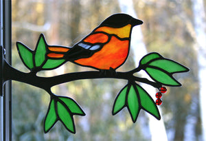 stained glass baltimore oriole on a window frame metal branch with red berries