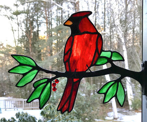 stained glass red cardinal on a window frame metal branch with red berries