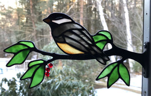 stained glass chickadee on a window frame metal branch with red berries