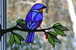 stained glass eastern bluebird on a window frame metal branch with red berries