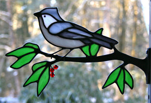 stained glass tufted titmouse on a window frame metal branch with red berries