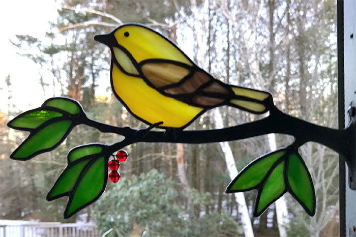 stained glass yellow warbler on a window frame metal branch with red berries