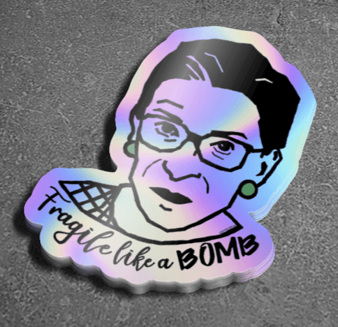 Vinyl sticker on holographic paper with drawing of Ruth Bader Ginsburg and text that says Fragile Like a Bomb