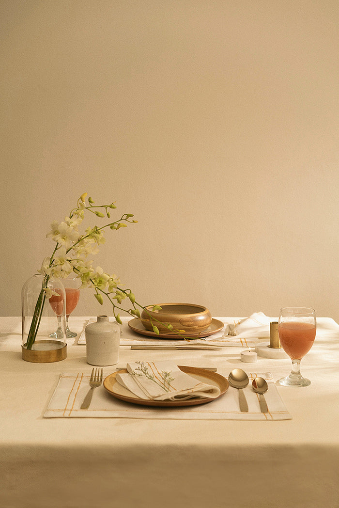 A romantic table setting with a set of handmade embroidery table linens and ceramics.