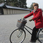 Patricia Belyea bicycling across the Imperial Palace grounds, Kyoto