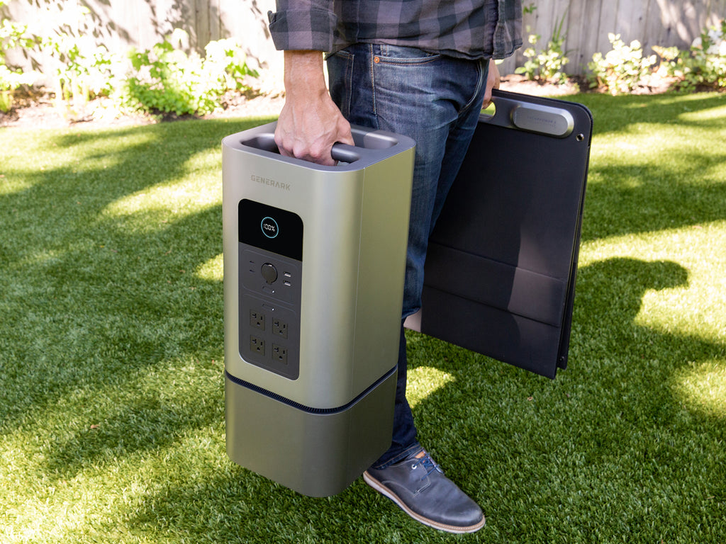 A man carries the HomePower 2 and SolarPower 2 by their integrated handles.