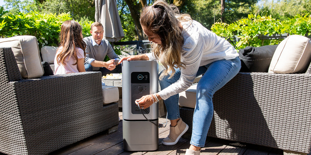 A woman plugs a device into the HomePower 2 backup battery generator on a back a patio.