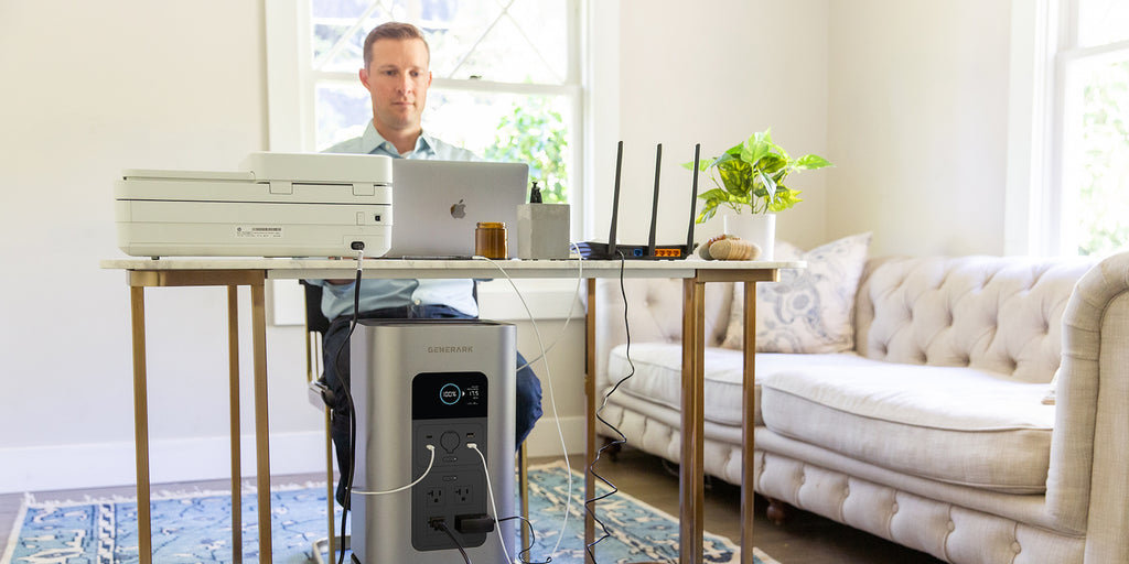 A man works at a desk in a home office powered by the HomePower backup battery power station.