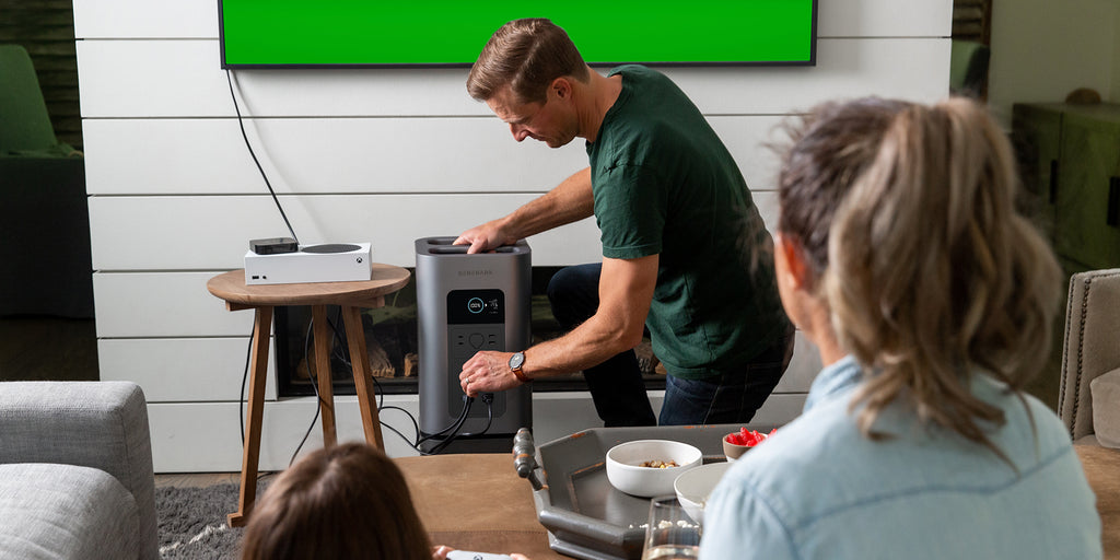 A man plugs an entertainment system into the HomePower 2 power station.