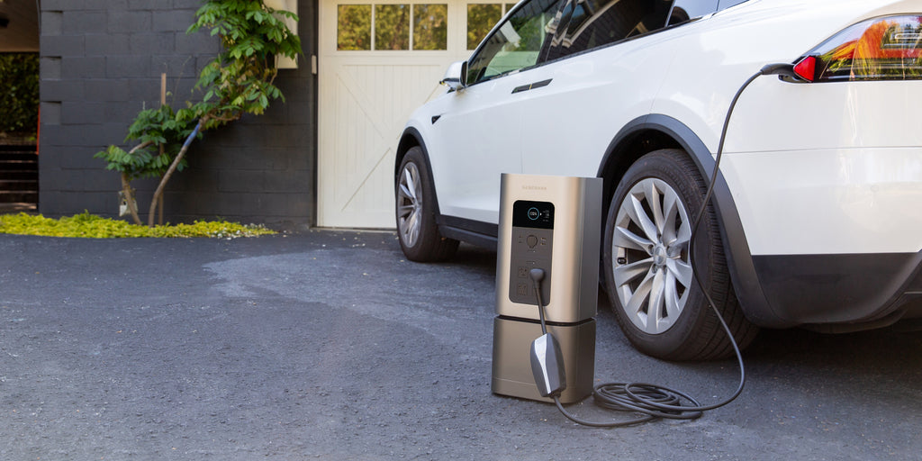 The HomePower 2 sits in a driveway charging from a carport.