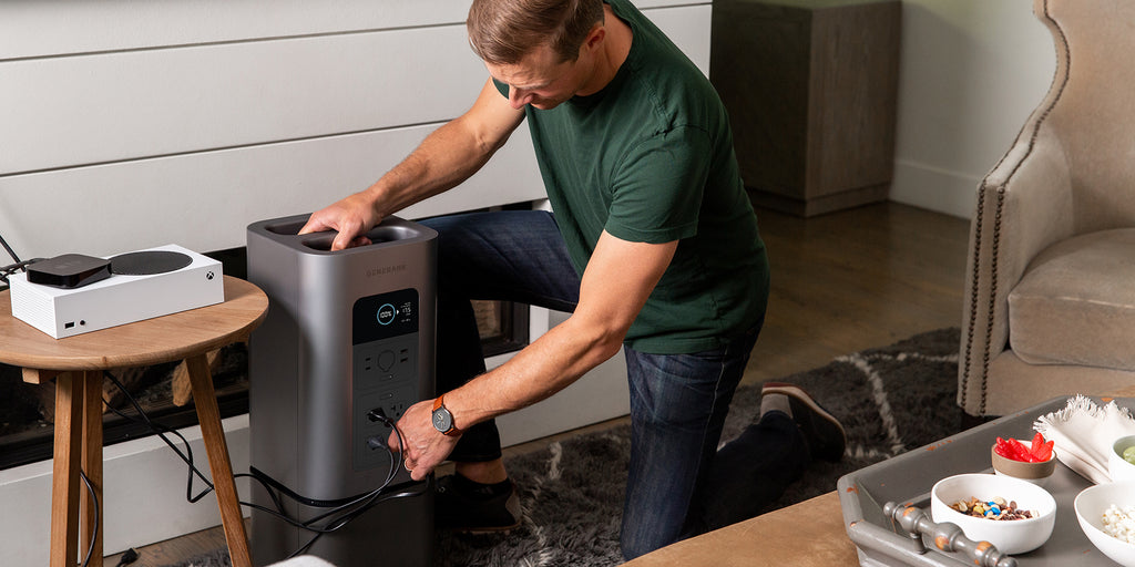 A man plugs an entertainment system into the HomePower 2 backup battery generator.