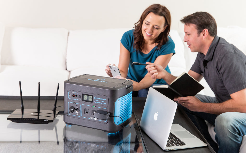 A man and woman read a message off a phone and use a laptop powered by the HomePower ONE emergency backup battery power station.