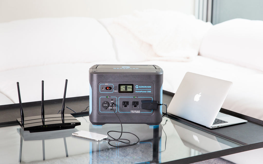 The HomePower ONE backup battery power station is pictured on a coffee table charging a cell phone, laptop, and powering a modem.