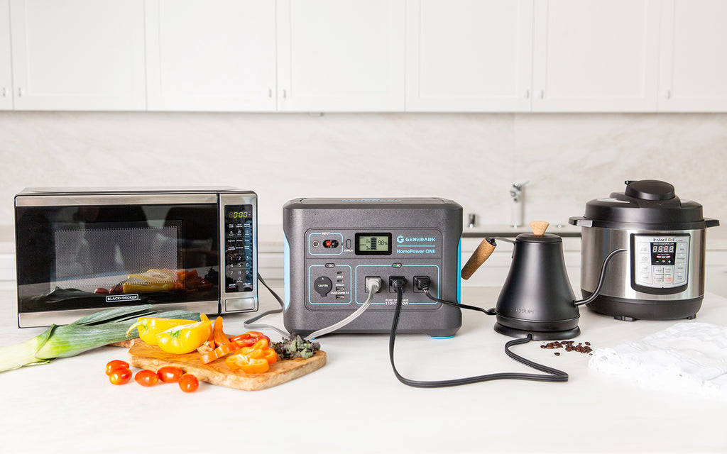 Sliced vegetables sit on the counter next to the HomePower ONE portable power station with a microwave, kettle, and slow cooker plugged into it.