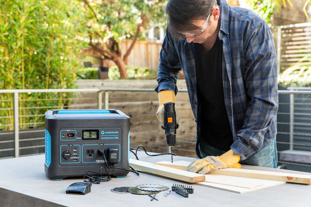 A man uses a power drill that is powered by the HomePower ONE backup battery power station.