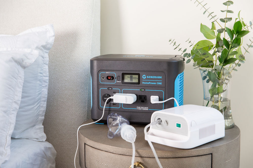 A CPAP machine is plugged into the HomePower ONE portable power station on a nightstand.