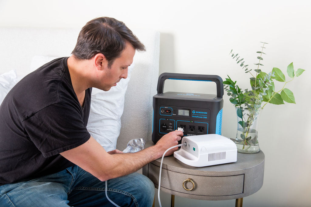 A man sits on a bed and plugs a CPAP machine into the HomePower ONE portable power station.