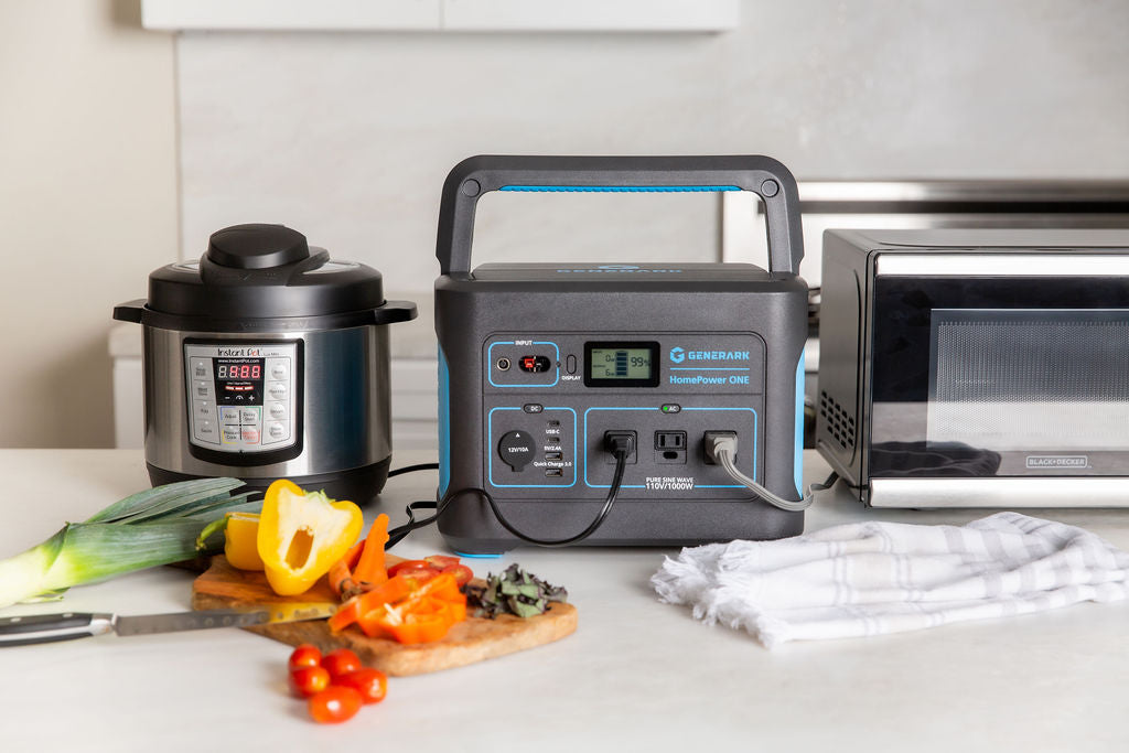 The HomePower ONE portable power station is pictured on a kitchen counter powering a slow cooker and microwave with sliced vegetables also on the counter.