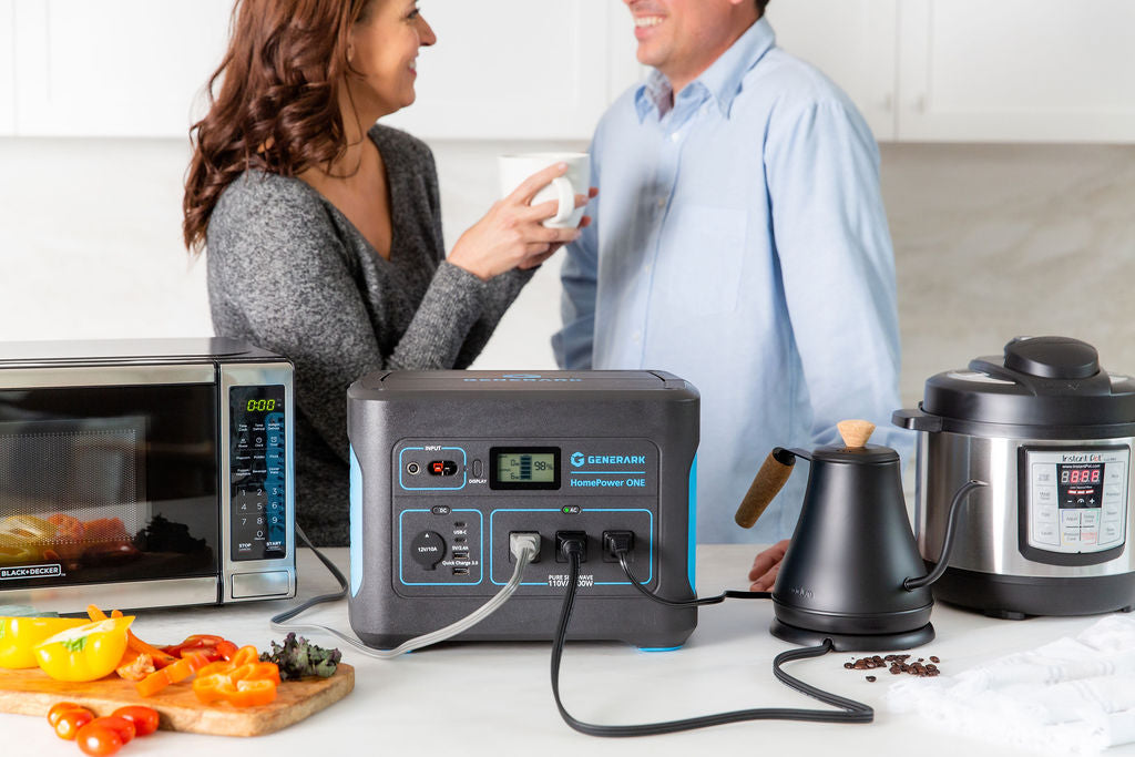 A man and women have a conversation in the kitchen with the HomePower ONE backup battery power station that is powering a microwave, kettle, and slow cooker.