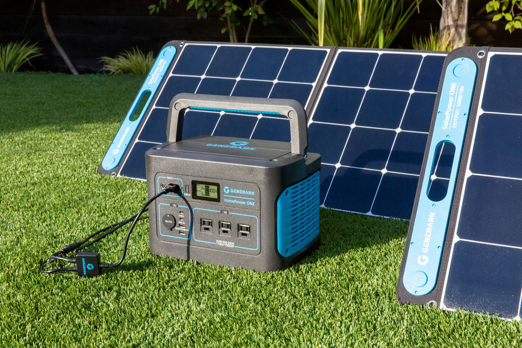 The HomePower ONE backup battery generator and SolarPower ONE solar panel power station are pictured on an outdoor lawn.