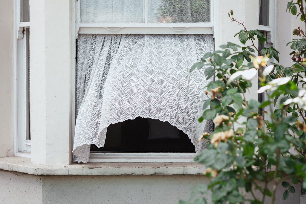 A window is open on a white house, with a white lace curtain blowing out the window.